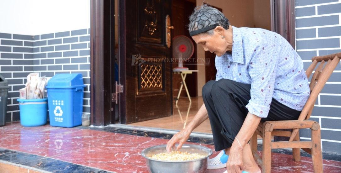 学宗溪村,79岁的曹寅珍坐在新家门前剥玉米。