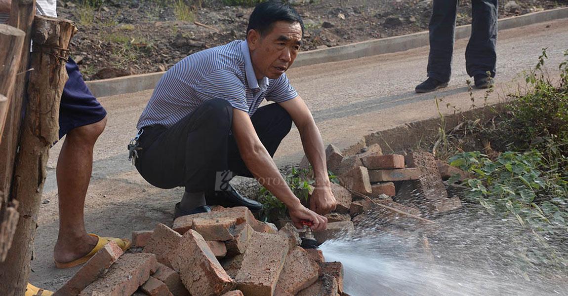 """""""龙头一拧水自来"""",村干部在检测新铺设的自来水管道,预计10月将实现自来水入户。"""