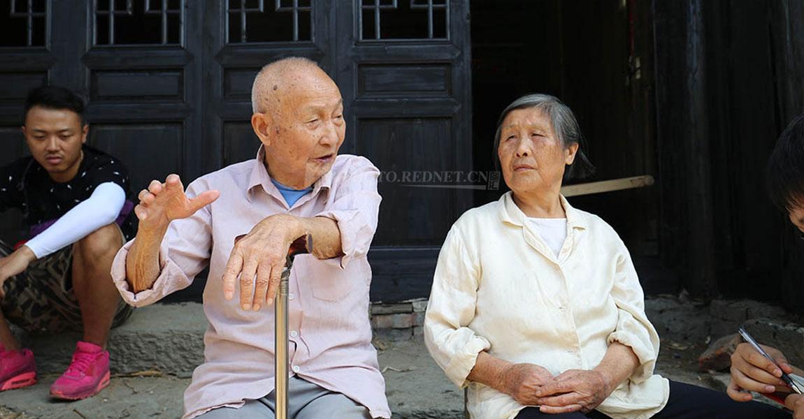 9月21日,通道县县溪镇红军街上,95岁的退休教师吴跃飞(中)和老伴一起讲诉82年前的红军长征路过通道时的见闻。