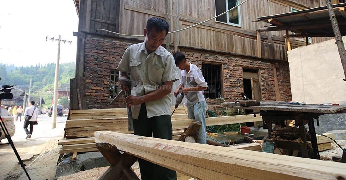 """通道县双江镇琵琶村。木匠杨正大带着儿子杨清华在""""加班"""",赶制村里的木质侗族风情宣传廊。"""