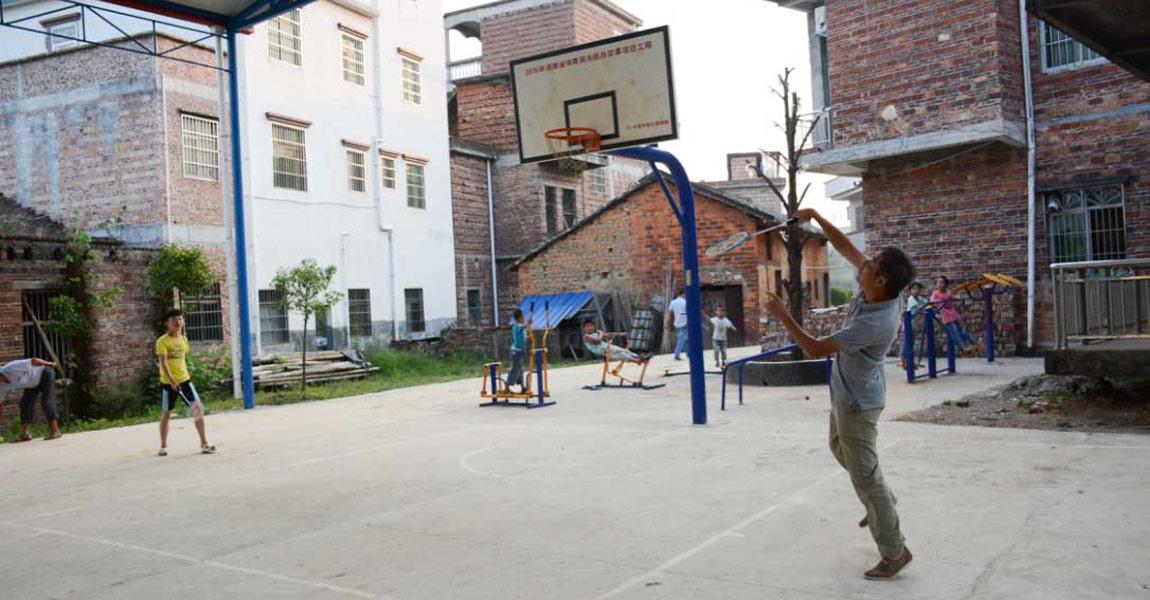 在村里新建的操场上,小孩大人们在打羽毛球。
