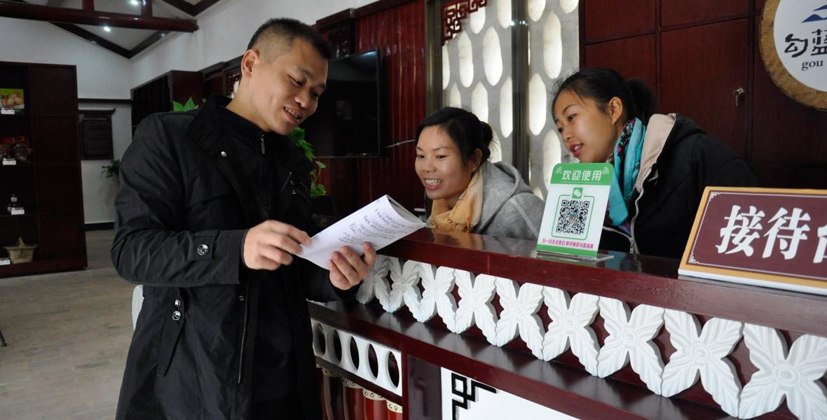 扶贫队长江晓军(左一)与导游探讨勾蓝瑶解说词。