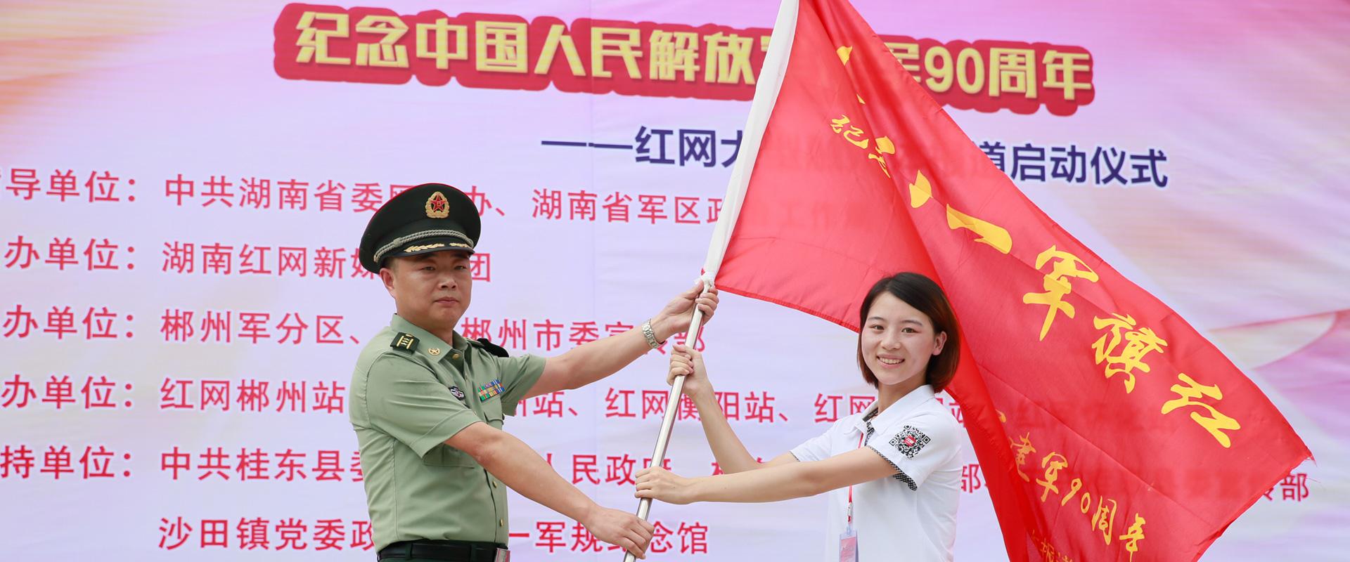 郴州军分区政治工作处主任张淼向采访团授旗。