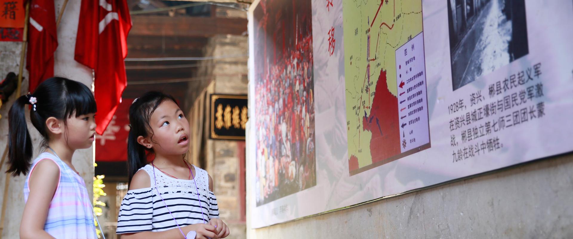 来自香港的黄军婷、黄美茵姐妹俩在资兴县苏维埃政府旧址参观