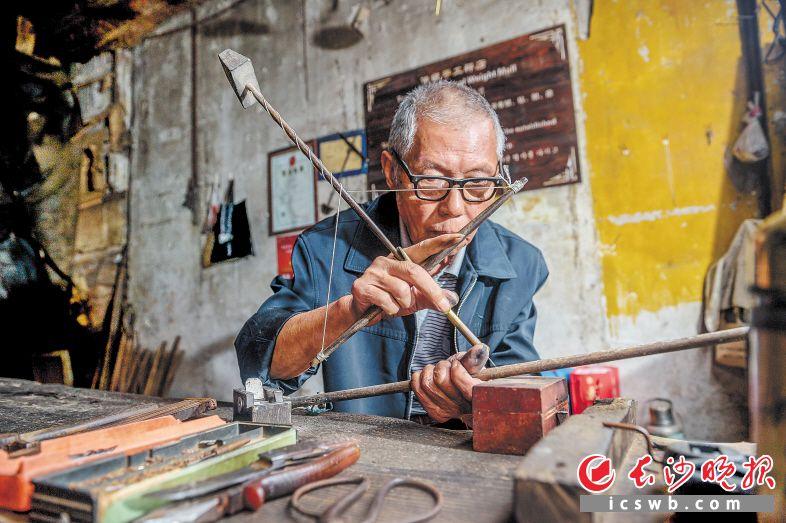 靖港镇老街上,79岁的吕定龙老人依然坚守着传承百年的手工制秤,每日戴着眼镜坐在家门口,用着自制的工具刻尺度。本组图片均为 陈飞 摄