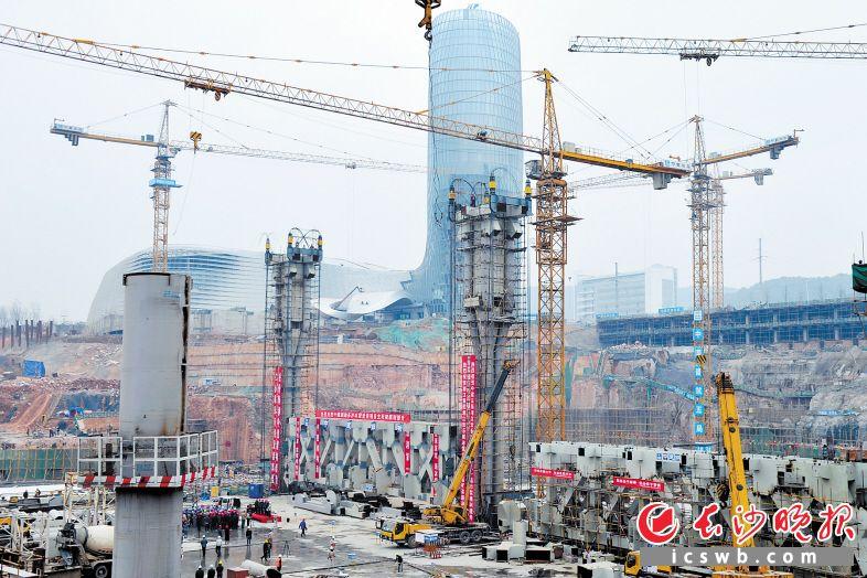 日前,湘江欢乐城欢乐雪域项目钢结构屋盖首榀主桁架正式提升到位,欢乐雪域钢结构进入全面施工阶段。 王志伟 摄
