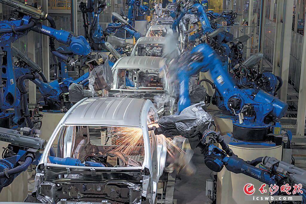 """比亚迪汽车生产车间内,机器人的""""魔术手""""替代了人工,精准作业。曾祥平摄"""