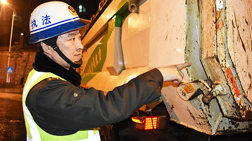 执法人员对出场的渣土运输车车厢的密闭性进行检查
