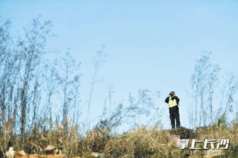 黄健雄在用望远镜进行瞭望观察,防止有人闯进高铁线路。