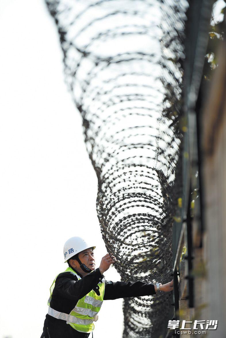 在一处铁路护栏附近,黄健雄仔细检查防护网固定情况。因为日晒雨淋,防护网可能存在生锈脱落的情况。