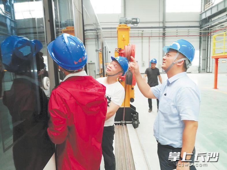 """↑在生产现场,谢耀征(右一)在对""""先锋号""""的技术细节进行指导。均为长沙晚报记者 王斌 摄"""