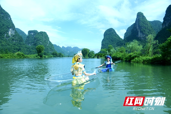 桂林千古情艺术团的演员们身着民族服饰,乘坐着透明小船,在桂林漓江上