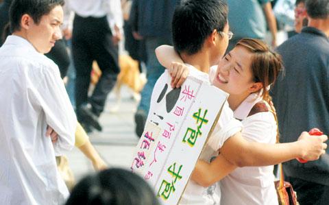 """10月29日,长沙市黄兴路步行街,女孩举着""""抱抱""""的纸牌向路人索要拥抱。当日,一个名为""""抱抱团""""的民间组织在长沙发起公益行为艺术活动记者伍霞摄"""