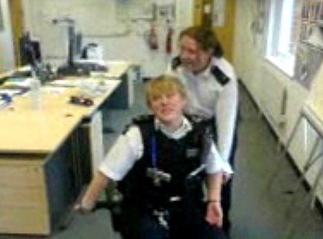 数名男警察合力将一名女警员用手铐铐在旋转座椅上,之后同事们连人