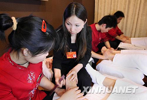3月2日晚,来自江苏的全国人大代表陆琴利用休息时间来到她在北京新开的脚艺店里看望员工并指导技师修脚。陆琴是江苏扬州市的一名普通修脚女工,利用一技之长,走上自主创业之路。目前她已在全国各地开办了近40家脚艺店,还开办脚艺职业专修学校,培训下岗、失业人员4000多人,并安排他们到各地就业。 新华社记者姚大伟摄