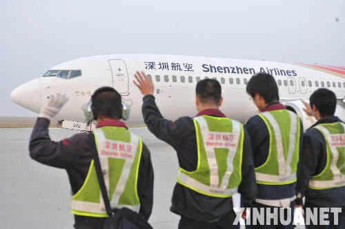 """12月15日,工作人员在深圳机场向即将起飞的飞机挥手致意。 当日早上7时20分,作为两岸直接""""三通""""首个飞往台湾的大陆航班,深圳航空ZH9095航班正式从深圳机场起飞。 新华社记者壮锦摄"""