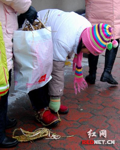 在鞋子上套上草鞋的小朋友,妈妈手中还提了一大袋