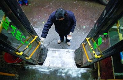 1月24日晨,长沙市高叶塘公交停车场,工作人员在对公交车的上下车台阶撒盐一方乘客滑倒
