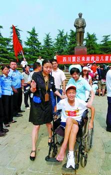 一个孩子坐在轮椅上参观毛泽东铜像广场。小刘军摄