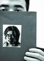 孙志刚是学美术的,他家人手中拿着的是孙志刚生前的自画像。