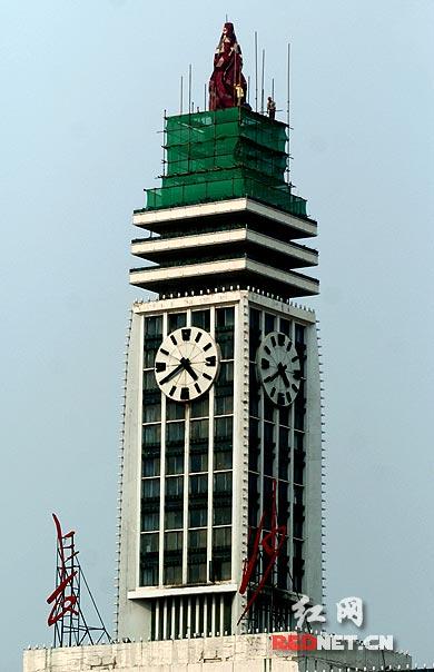 """为迎接新中国成立60周年大庆,工人们在长沙火车站钟楼塔顶搭建脚手架,准备对""""红辣椒""""进行清洗维护。"""