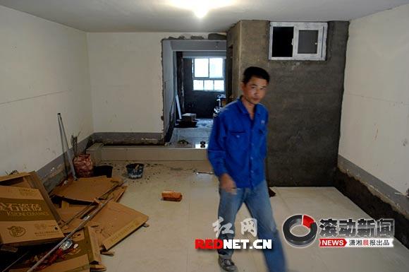 记者询问一名正在车库内搞装修的师傅