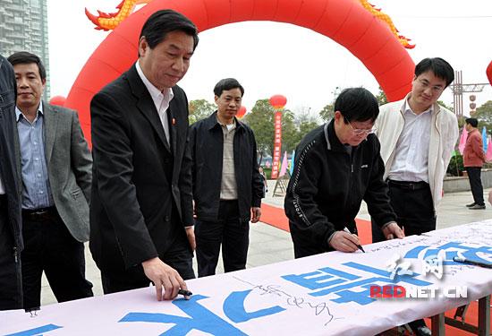 """湖南省人大常委会副主任蔡力峰在""""爱护母亲河珍惜水资源""""倡议书上签上自己的名字。"""