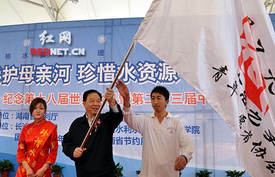 """省政协主席阳宝华为长沙理工大学""""大禹之子""""志愿者授旗。"""