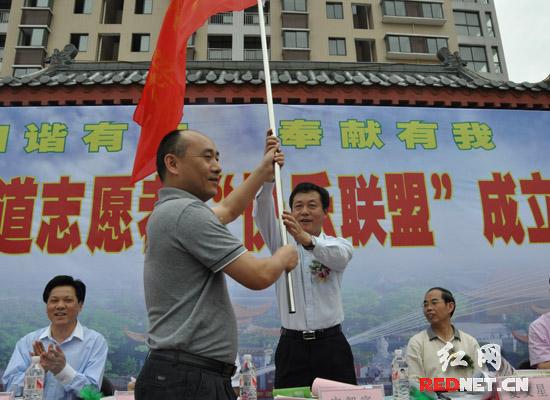 """湖南省文明办主任宋智富(右)出席活动并为""""快乐联盟""""服务队授旗。"""