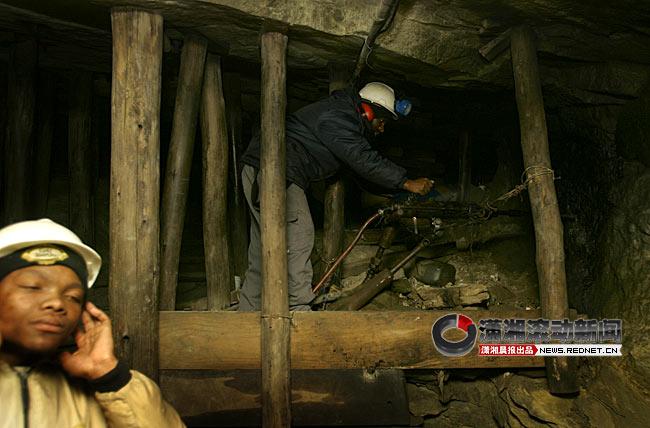 一名工人在演示当年挖矿场景,机器钻石头发出的轰鸣声让前面的导游赶紧捂上了耳朵。图/潇湘晨报南非特派记者 华剑   红网南非约翰内斯堡6月17日讯(潇湘晨报特派记者 柳宝来)据说1886年的一天,一位失意的澳大利亚淘金者查理森,在约堡的山坡上苦闷地走来走去。突然,一块石头险些将他绊倒,他恼怒地用脚踢了它。但当他定睛观瞧这块石头时,竟然眼前一亮不错,这是一块含金量极高的金矿石,约堡这个当初的小山村,就是因它而逐渐兴旺起来,而今更是成为南非最大的城市,还是南非的经济中心。      要真正了解约翰内斯堡的历