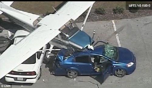 这架单引擎飞机正好落在了两辆汽车上.高清图片