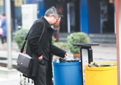 一位市民主动将垃圾丢进垃圾桶里