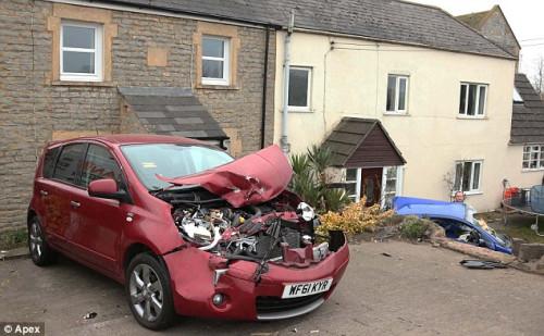 两辆撞碎的汽车分别停在两栋农舍前