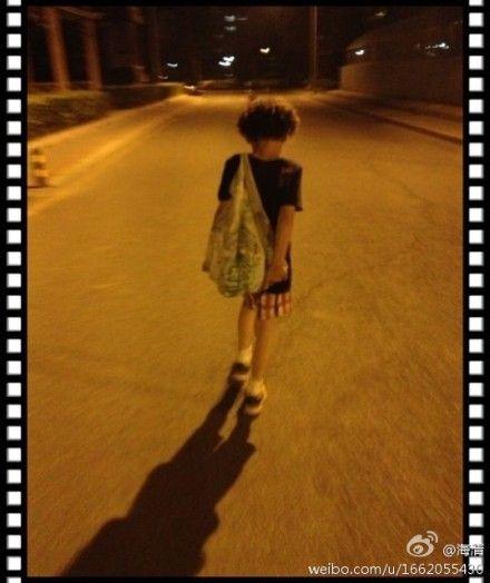 """""""照片晒出的是爱子的背影照,小家伙一头卷发,穿着黑色t恤红白格子短裤"""