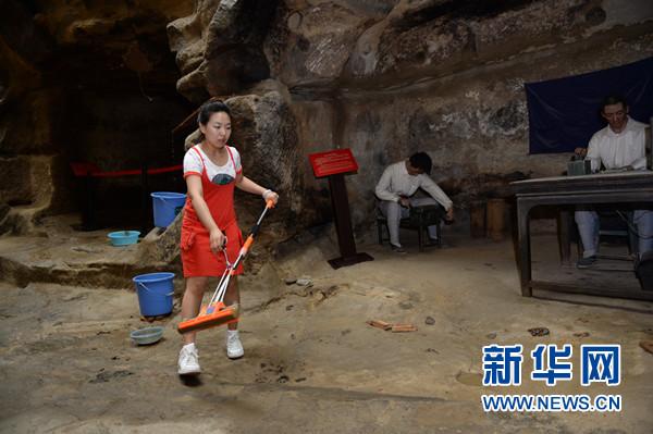 7月13日,工作人员在延安新闻纪念馆清理山体中下渗的雨水。新华社记者 李一博摄