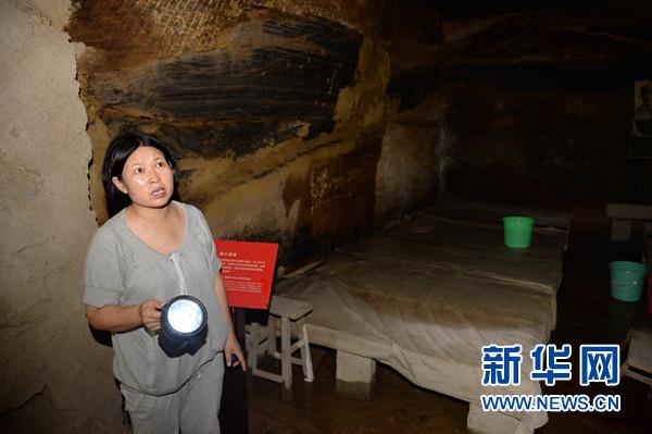 7月13日,延安新闻纪念馆馆长刘妮查看石窟旧址内的渗漏情况。新华社记者李一博摄