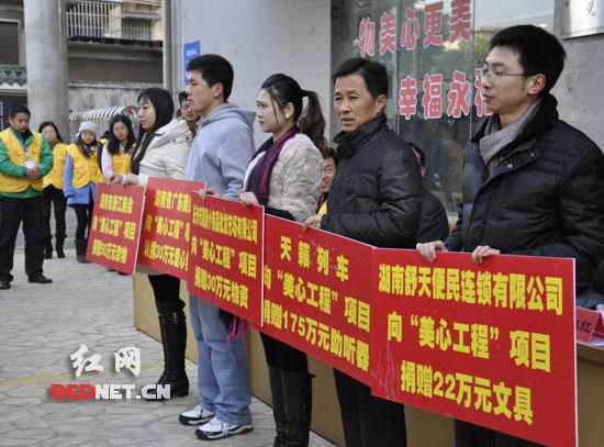 """启动仪式现场,湖南舒天便民连锁有限公司等爱心企业向""""美心工程""""举牌捐赠款物。"""