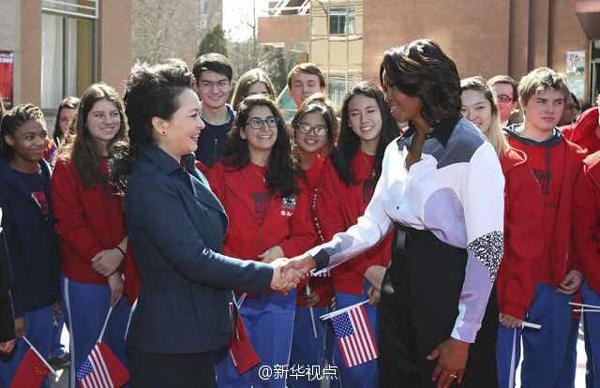 """新华网北京3月21日电 据新华社""""新华视点""""微博报道,21日上午,习近平主席夫人彭丽媛与奥巴马总统夫人米歇尔一起来到北师大二附中参观。教学楼前,学生们手挥两国国旗,热情欢迎两国元首夫人。"""