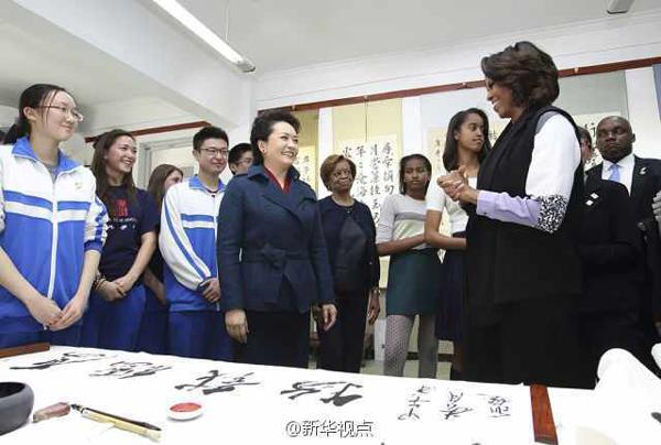"""彭丽媛和米歇尔走进美术教室,中外学生正在上中国书法课。应学生邀请,彭丽媛欣然提笔,挥毫写下""""厚德载物"""",并赠送给米歇尔。"""
