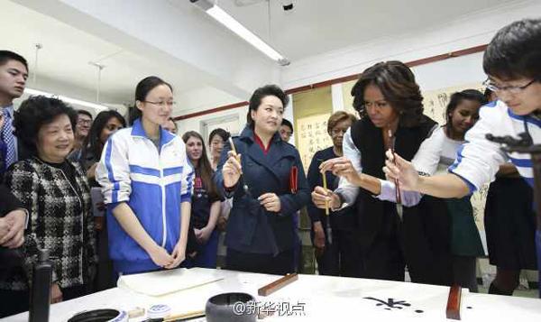 """米歇尔和学生一起临摹汉字""""永"""",彭丽媛在旁拿起毛笔示范握笔。米歇尔连着写了两个""""永""""字,直夸中国书法太美了,说自己还要多练习。"""