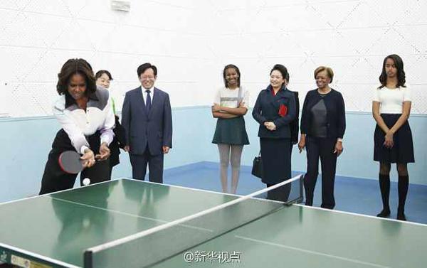 """在北师大二附中的体育馆里,彭丽媛和米歇尔与学生们一起感受乒乓球运动的魅力。米歇尔与教练试着挥拍对打。彭丽媛提起40多年前的中美""""乒乓外交""""。"""