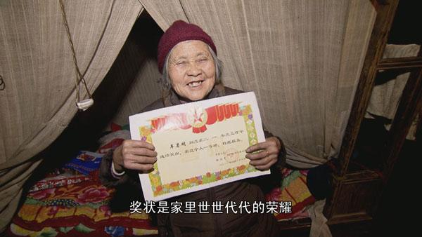 85岁妈妈的蚊帐很旧;手捧儿子车著明立功的奖状笑开了花
