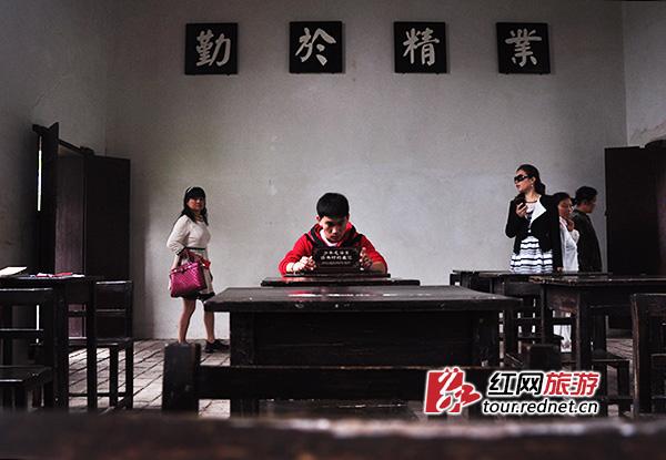 """东山书院的教室里,一位男生坐在毛泽东曾经坐过的座位上,后面的墙上写着""""业精于勤""""四个大字。这个教室建于1905年,是东山书院建筑中唯一一栋具有西洋风格的房子,窗户高且大,两块黑板还可以上下移动。少年毛泽东在戊班学习。当年,16岁的毛泽东因个高坐在第二排倒数第二位。置身其中,仿佛能听到朗朗的读书声。"""