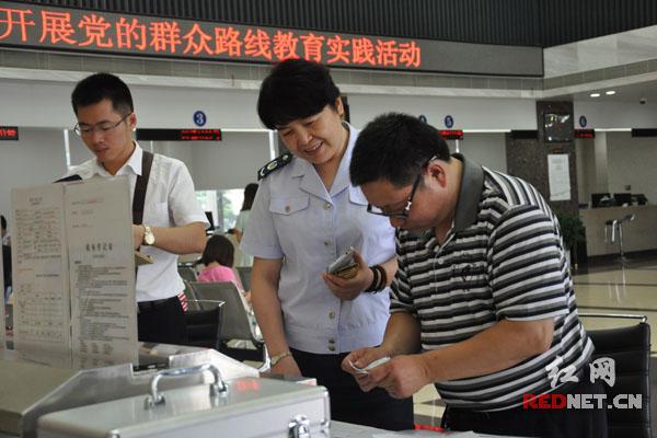 宁乡地税党组书记、局长黄京沙当天在大厅值班,正辅导纳税人办理涉税业务。