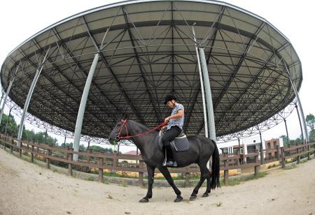 邹麟/立秋后,长沙县新江现代生态农庄的马场里,游客在赛道上骑马策...