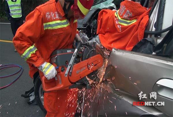 消防官兵利用切割机对驾驶室车门进行破拆