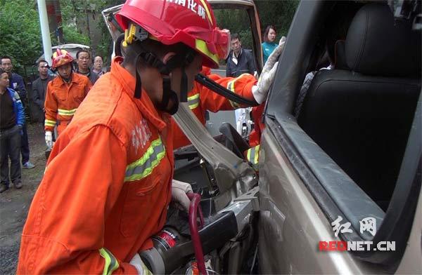 消防官兵利用液压扩张剪对驾驶室车门进行破拆