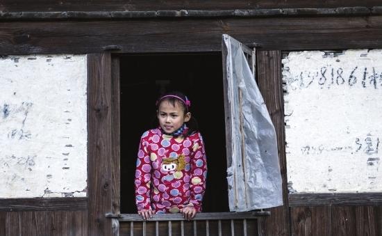 (新化县槎溪镇新群村,8岁的杨菊英站在窗前。杨菊英3岁时,在长沙打工的父亲因车祸身亡,母亲忍受不了贫困,出走后一直未归。现在杨菊英与66岁的奶奶相依为命。