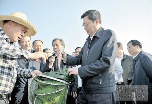 11月14日,在湘江边的竹埠港综合排污口,杜家毫(前右一)现场查看垂钓者钓上的河鱼。