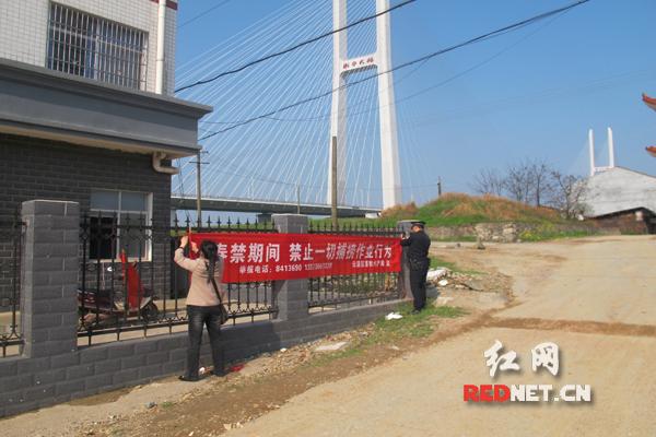 民警和渔政工作人员悬挂宣传横幅